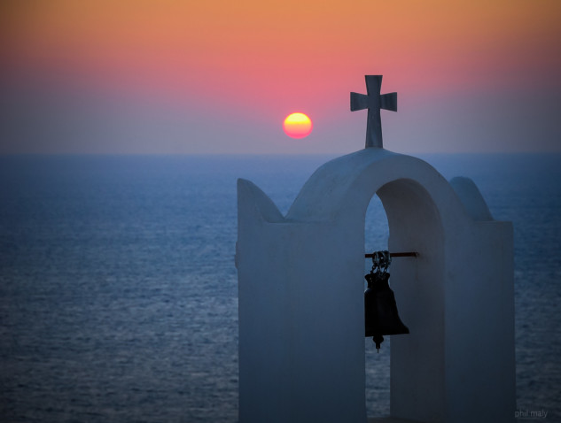 Chapel with cross and bell with a sunset over the sea in the background