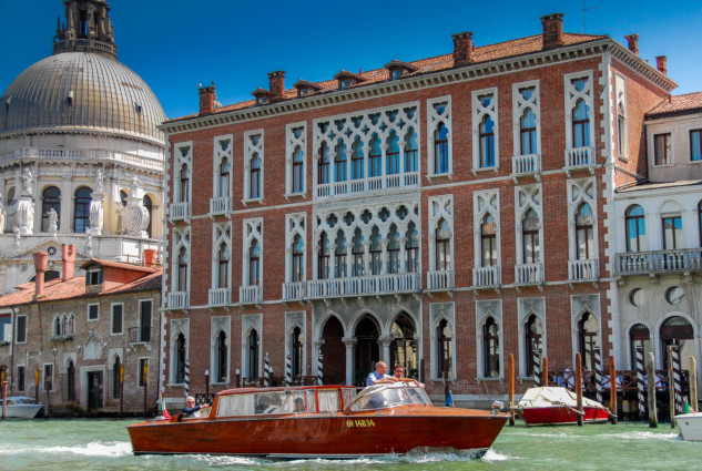 Venitian palace on the Grand Canal with a wooden boat in front
