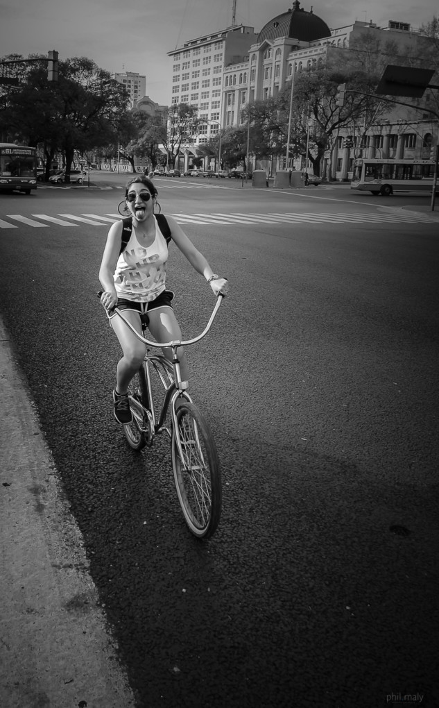 Street portrait of a young lady on her bycicle pulling out her tongue at the camera