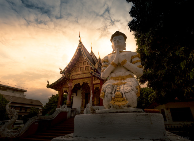 Praying Buddha in front of a temple at sunset