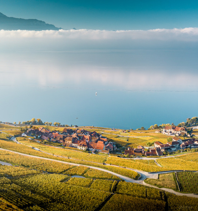 A village of the Lavaux in the foreground and the lake covered with clouds in the background
