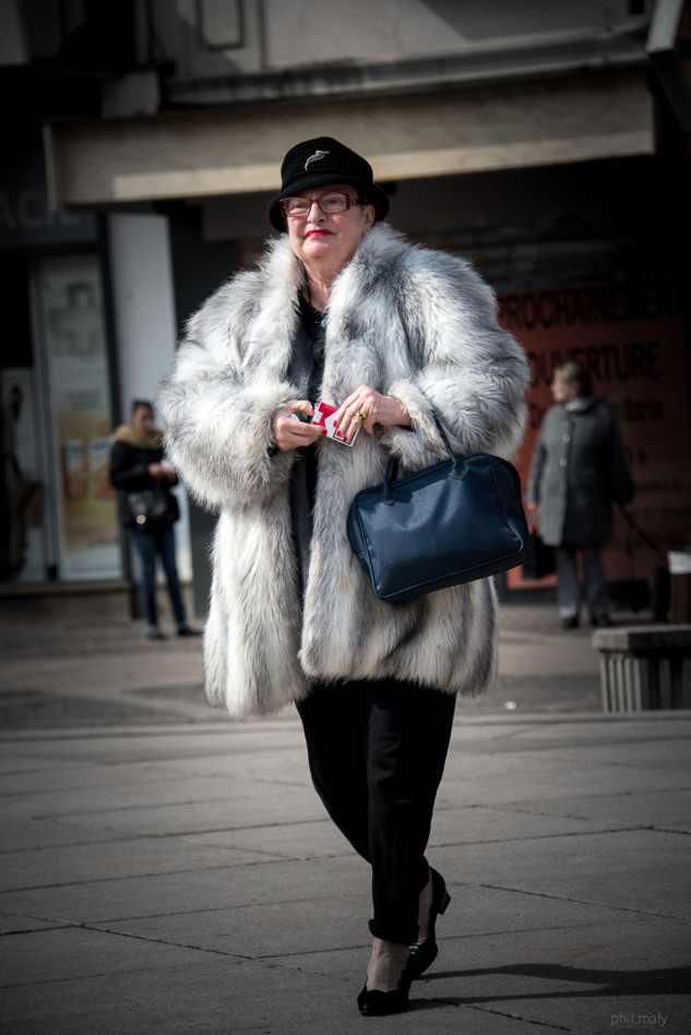 Street portrait of an old lady wearing a fur coat and taking out a cigarette