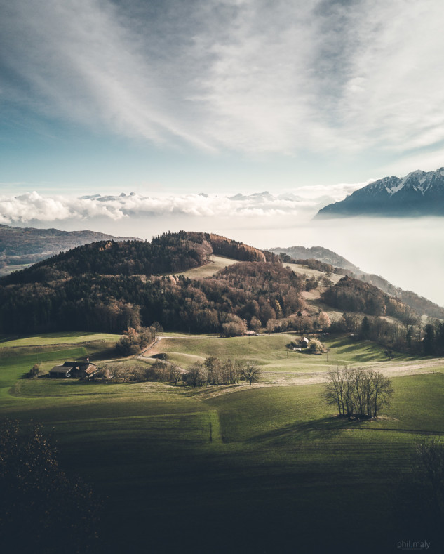 Drone shot of hills with the mist covering the lake Leman and mountains in the background